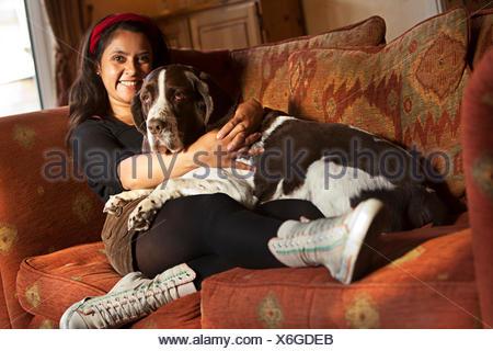 Donna seduta sul divano con il suo cane Foto Stock