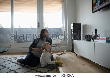 Gravidanza madre e figlia toddler guardare la TV sul soggiorno piano Foto Stock