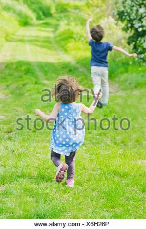I bambini in esecuzione sul percorso attraverso la campagna Foto Stock