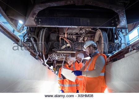Istruttore e apprendisti sotto il treno in railway engineering facility Foto Stock