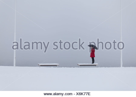 Figura solitaria di una giovane donna che indossa un cappotto rosso con ombrello in piedi su una panchina nella neve Foto Stock