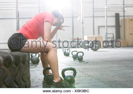 Esaurito donna seduta sul pneumatico in palestra crossfit Foto Stock