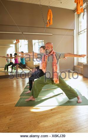 Persone che fanno il guerriero pongono in classe di yoga