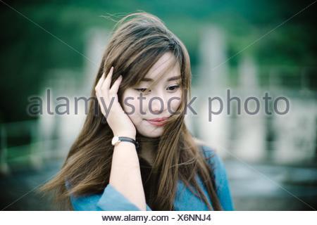 In primo piano della giovane donna sorridente mentre guardando verso il basso Foto Stock