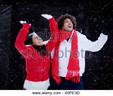 Felice coppia giovane a giocare nella neve sul giorno di inverno Foto Stock