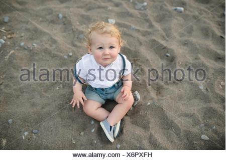Ritratto di overhead dei maschi di bimbo seduto sulla sabbia Foto Stock