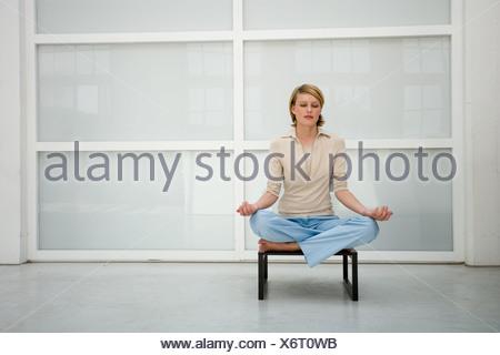 Imprenditrice meditando su uno sgabello foto & immagine stock