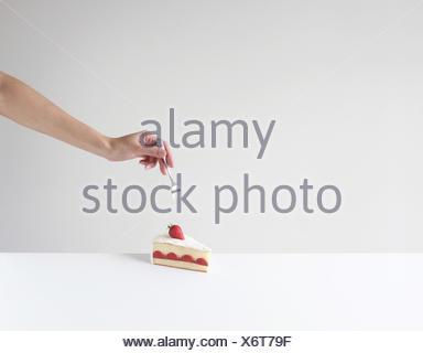 Mano che tiene una forcella circa a mangiare una fetta di torta Foto Stock