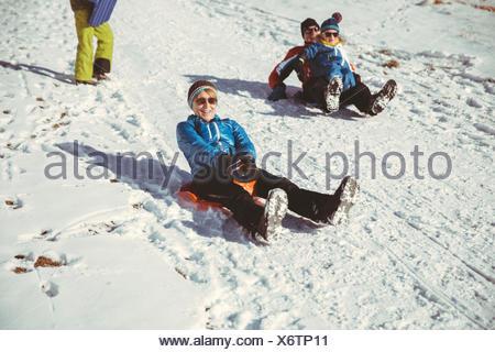 L'Italia, Val Venosta, Slingia, famiglia slitta verso il basso una collina nevoso Foto Stock