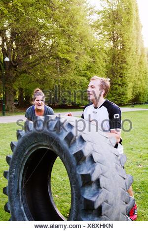 L uomo e la donna facendo pneumatico-flip esercizio presso il park Foto Stock
