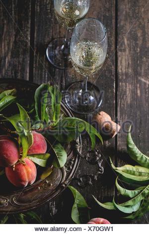 Le pesche sul ramo con foglie in piastra vintage e due bicchiere di champagne con sughero sopra il vecchio tavolo in legno. Scuro in stile rustico. Foto Stock