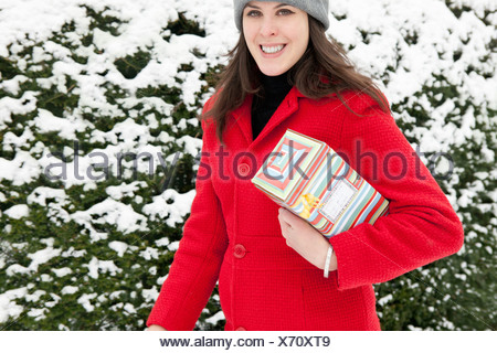Donna che trasportano dono avvolto nella neve Foto Stock
