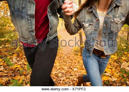 Ritagliato shot romantica di coppia giovane in esecuzione attraverso la foresta di autunno Foto Stock