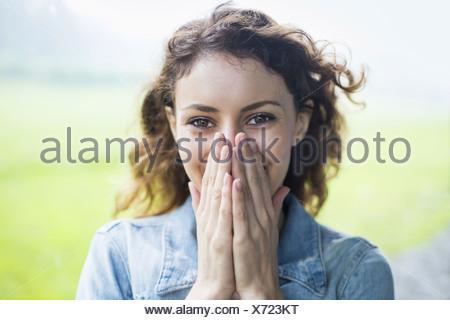 Una giovane donna in un paesaggio rurale con battente capelli ricci. Che copre il volto con le mani e ridere. Foto Stock