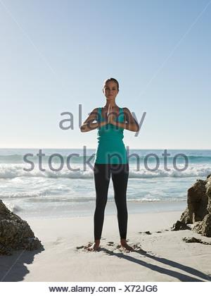 Giovane donna fare yoga sulla spiaggia