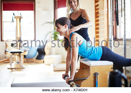 Giovane studentessa spingendo verso l'alto dal combo chair in palestra pilates Foto Stock