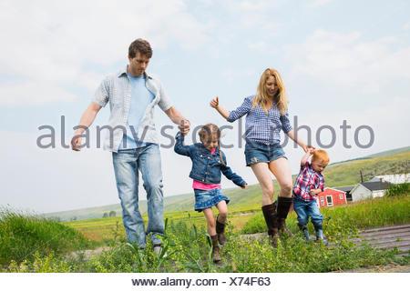 Famiglia passeggiate in campo rurale Foto Stock