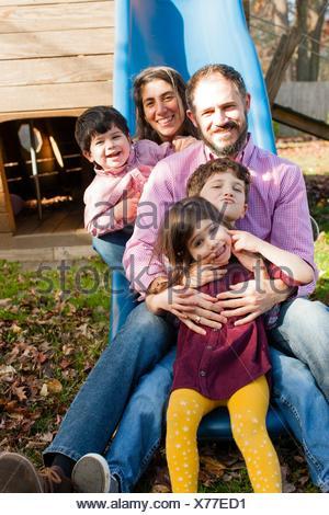 La famiglia in una riga tra ogni altri gambe sul parco giochi diapositiva, guardando alla fotocamera a sorridere Foto Stock