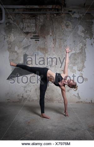 Metà donna adulta la pratica della mezza luna in studio di yoga, Monaco di Baviera, Germania Foto Stock