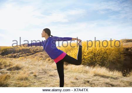 La donna a praticare yoga nel soleggiato campo rurale Foto Stock