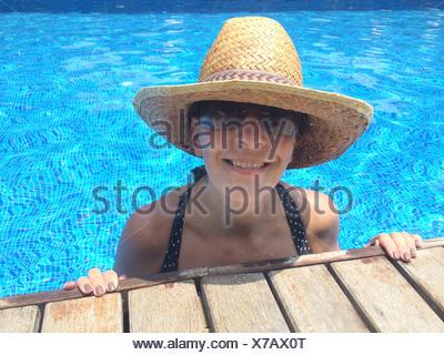 Donna sorridente in piscina, indossare un cappello di paglia Foto Stock