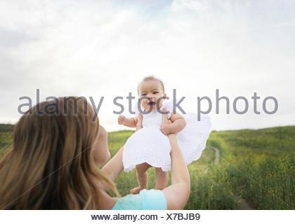 Sollevamento madre bambina in aria Foto Stock