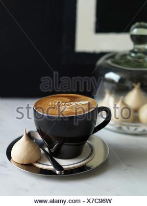 Tazza di cappuccino e una piccola meringa Foto Stock