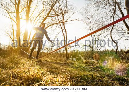 Giovane uomo in equilibrio su una gamba sulla slackline nel paesaggio di campo Foto Stock