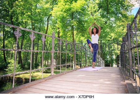 Donna fare esercizi yoga in un parco Foto Stock