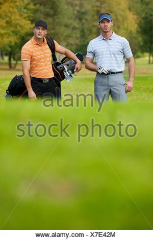 Giovani uomini in piedi sul campo da golf borse e zaini Foto Stock