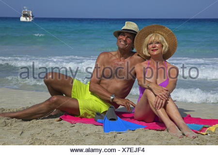 Coppia di anziani seduti sul telo da spiaggia a spiaggia sabbiosa, Balearen, Ibiza Foto Stock