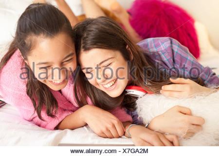 Le ragazze adolescenti a ridere guardando il computer portatile Foto Stock
