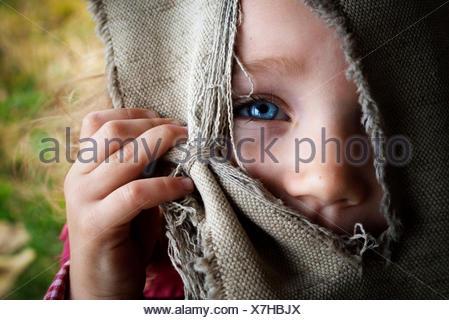 Ritratto di ragazza (4-5) volto nascosto dietro la cortina Foto Stock