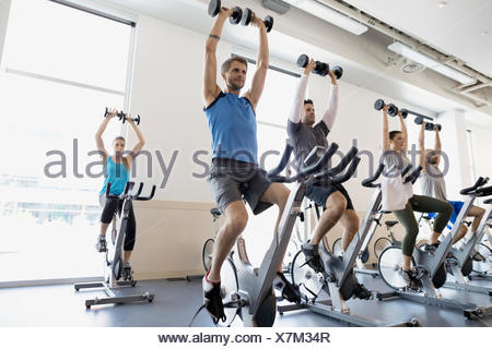 Classe di spin holding barbells overhead cyclette palestra Foto Stock