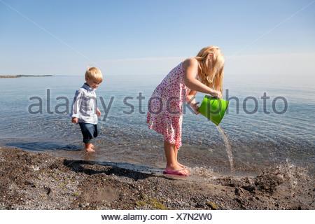 Ragazza giovane e suo fratello giocando sulla spiaggia dal lago Ontario;Ontario Canada Foto Stock