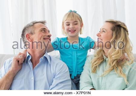 La famiglia felice rilassante sul lettino Foto Stock