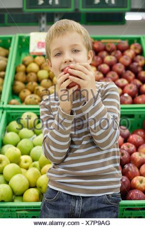 Giovane ragazzo in drogheria mangiare apple Foto Stock
