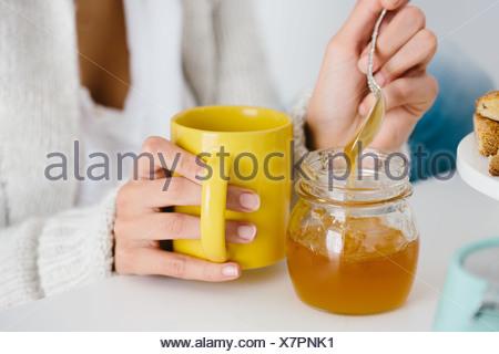 Giovane donna con drink di miele Foto Stock