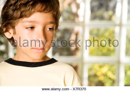 Un giovane ragazzo che guarda triste Foto Stock