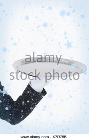 Il gloved bianco mano che tiene un vassoio d'argento Foto Stock