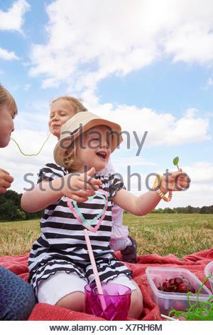 Tre bambine con dolci su un prato Foto Stock