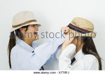 Ragazza adolescente tirando hat oltre il suo amico del volto, ridendo Foto Stock