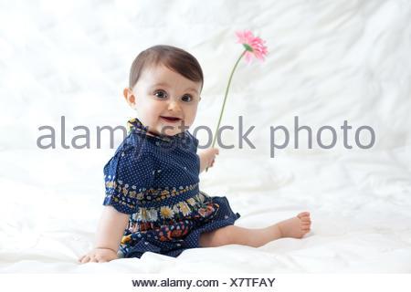 Ritratto di simpatici baby girl (6-11 mesi) giocando con fiore Foto Stock