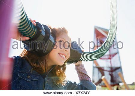 Ragazza che gioca ascoltando tubi nel soleggiato parco giochi Foto Stock