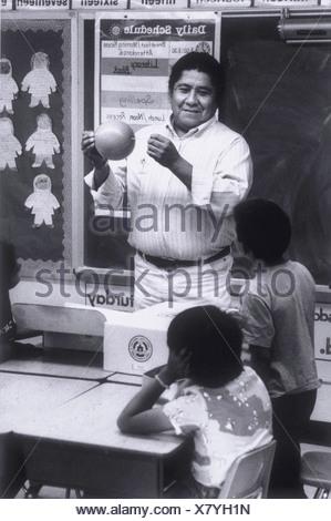 cc078403d1db Insegnante di scuola dando lavoro per studente; Un nativo americano  insegnante maschio con opere di primo grado gli studenti di una scuola  elementare