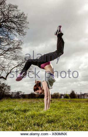 Donna facendo handstand con gambe divaricate Foto Stock