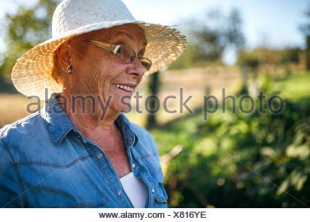 Ritratto di sorridere senior donna con cappello di paglia nel suo giardino  Foto Stock 9176675fbf99
