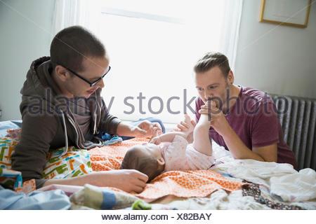 Coppia omosessuale giocando con il bambino sul letto Foto Stock
