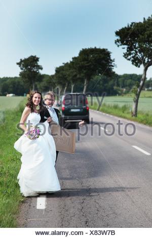 Coppie in viaggio di nozze il sollevatore escursionismo su strada Foto Stock