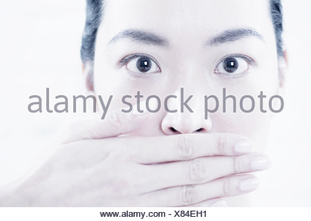 Close up della donna che copre la bocca Foto Stock